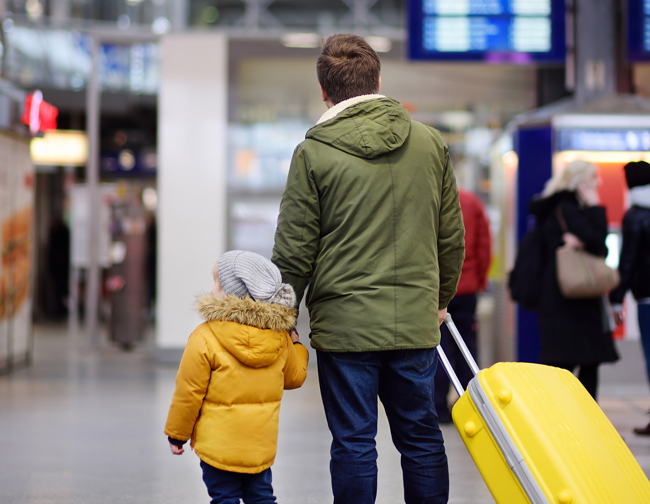 Father and son at airport looking at delayed flights