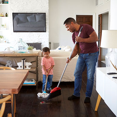 Man cleaning his house with his son before they leave on a vacation.