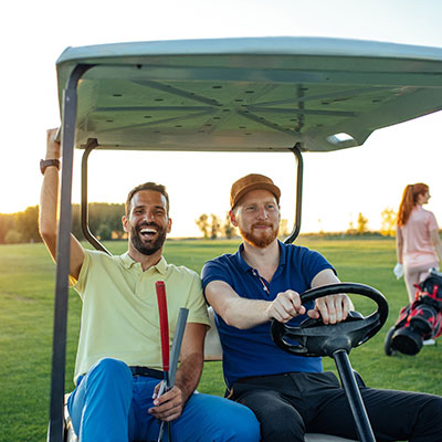People driving golf cart at golf course.