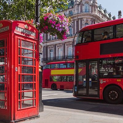 London, England tour bus passing a telephone booth.