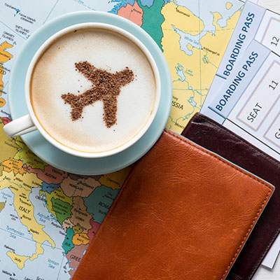 Airplan in chai tea latte, on top of boarding passes and map of Europe.