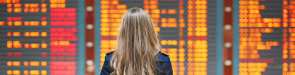 Woman staring at flight board full of cancelled flights.