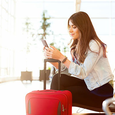 Woman with travel insurance sits in airport with her suitcase