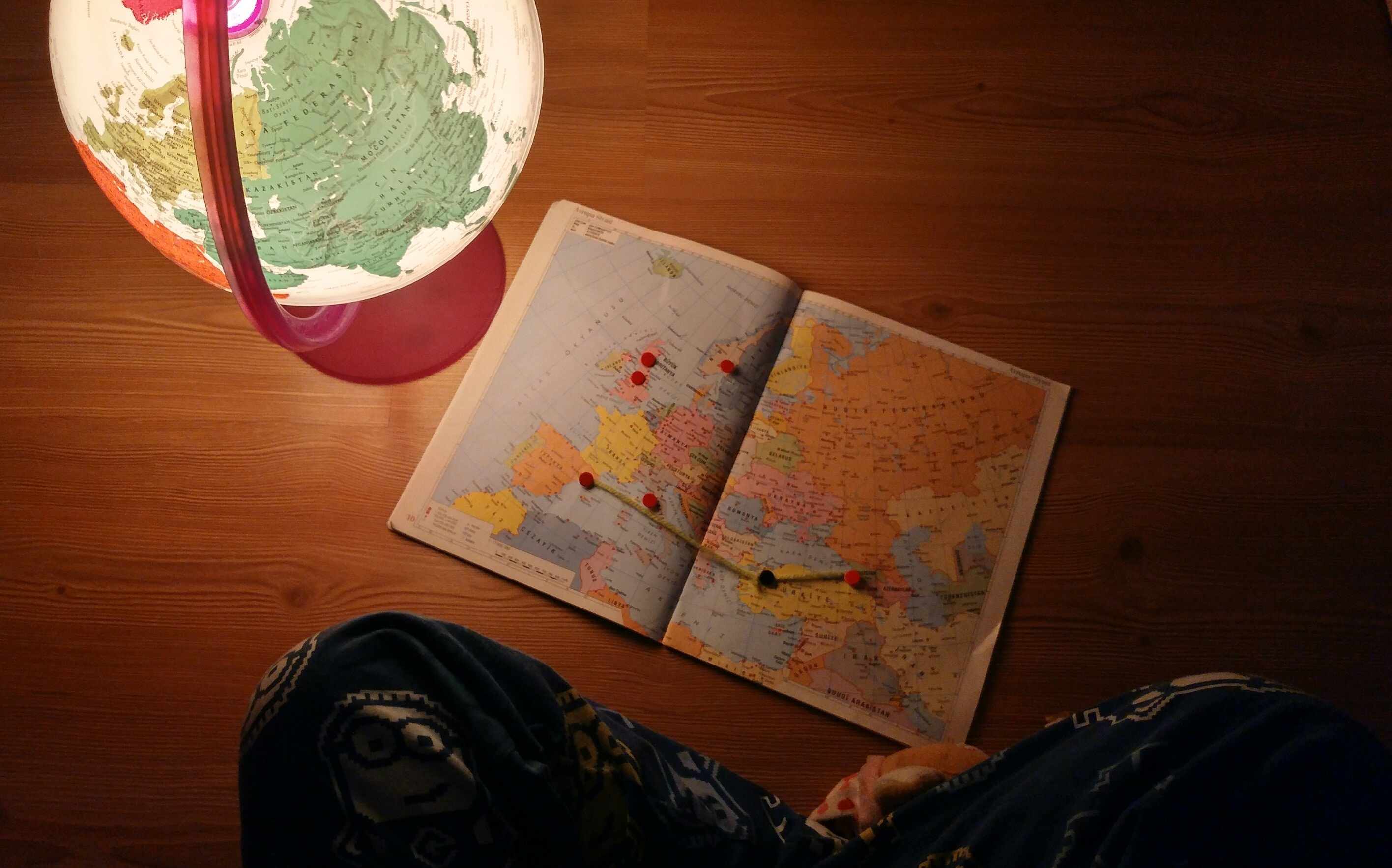 person-sitting-with-map-and-globe