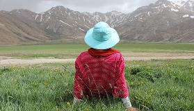 Woman-sitting-on-the-grass-in-front-of-mountains