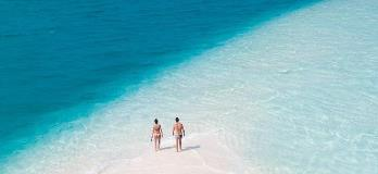 A-honeymooning-couple-walks-on-the-beach-reflecting-on-their-travel-insurance-purchase