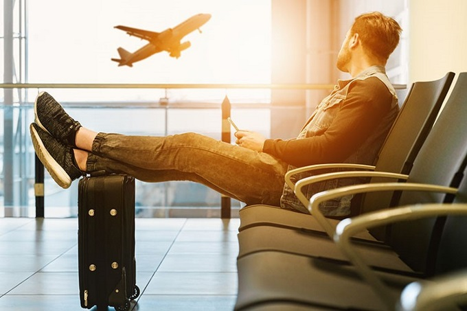 Man-watches-airplane-take-off-in-airport