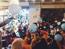Group-of-adults-throwing-blue-balloons-up-in-air