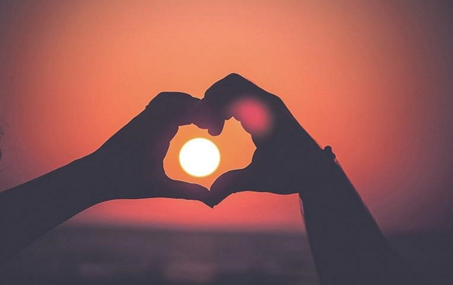 A-couple-with-travel-insurance-makes-a-heart-at-sunset