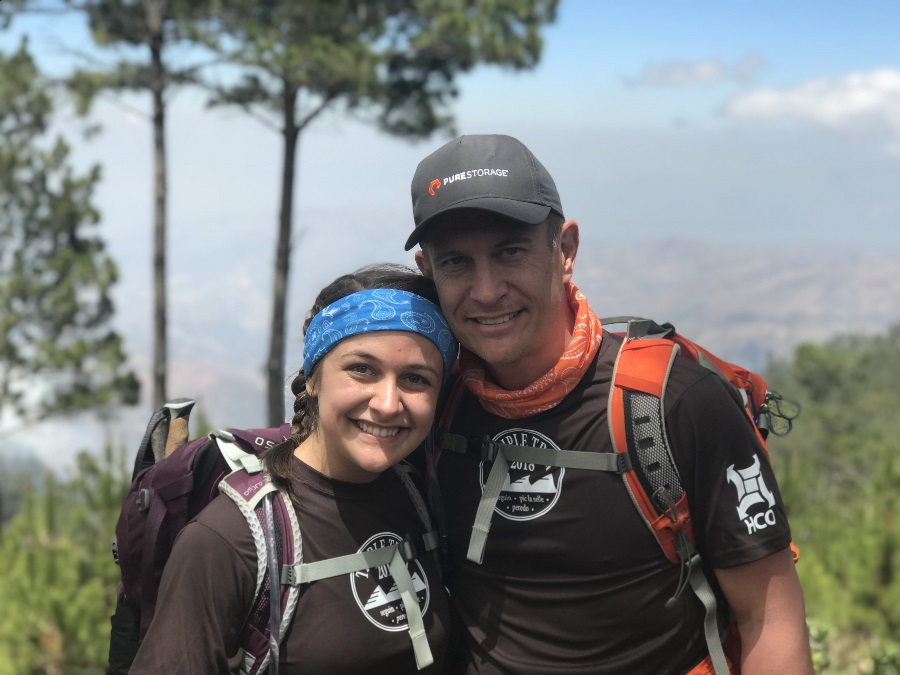 Father-daughter duo with travel insurance stops for a picture on hike