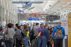 Crowd of people stands in line at airport