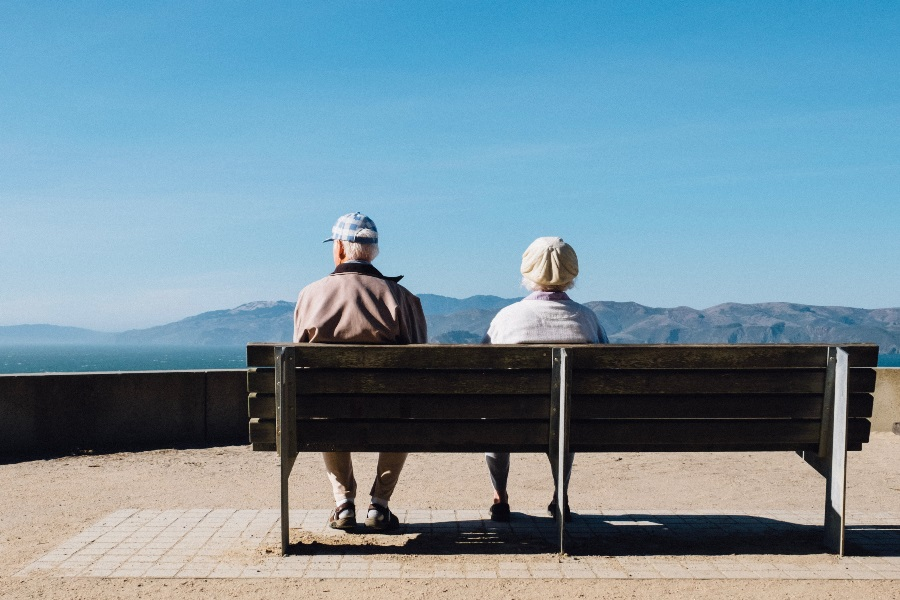 Baby-boomer-travelers-sit-on-bench-during-vacation