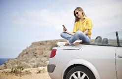 Student-sits-on-car-with-phone