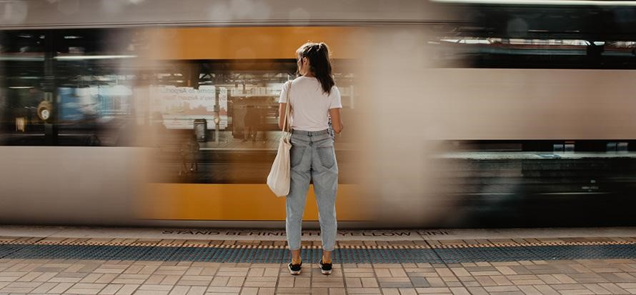 A-travel-insured-woman-stands-by-a-train