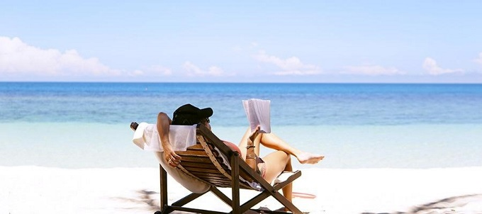 A-person-with-travel-insurance-reads-on-the-beach